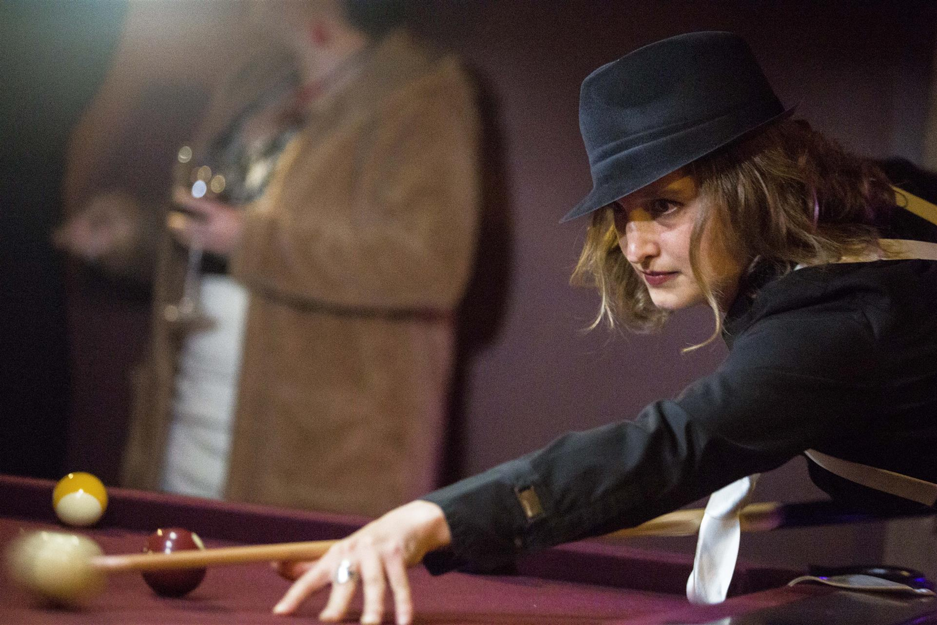 lady dressed in 1920s era clothes playing pool