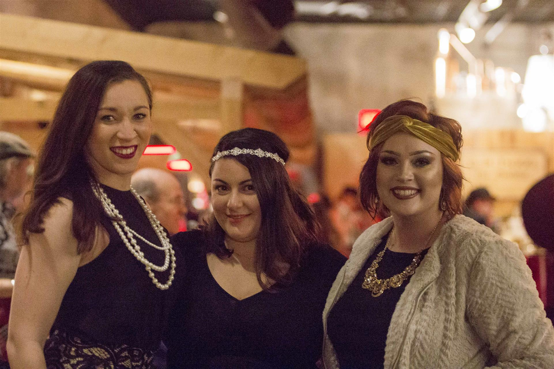 three women dressed in flapper outfits posing for pictures