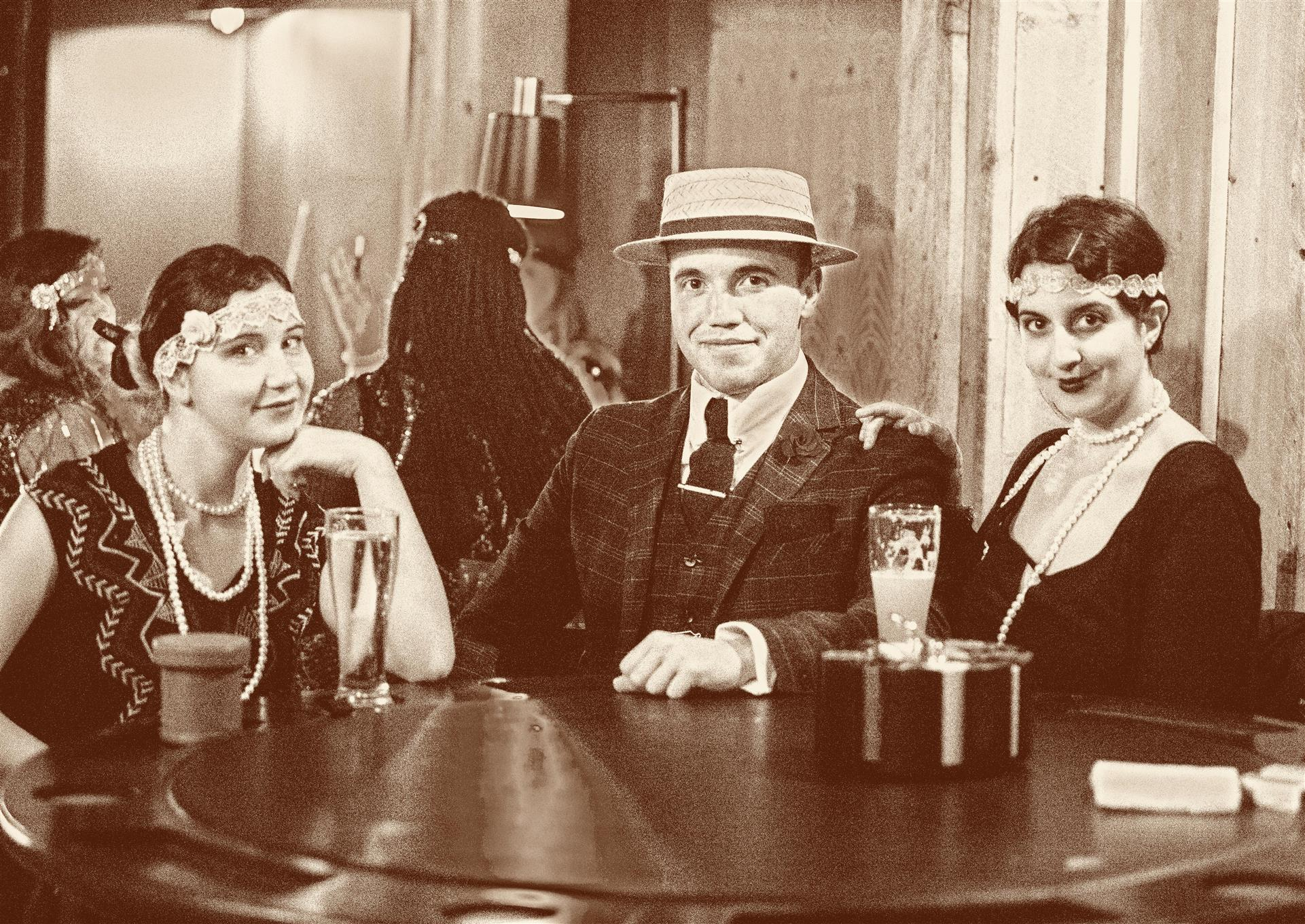 1920s picture of two women and a man sitting at a table