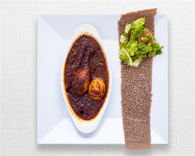 A drumstick or thigh slow cooked stew with berbere, onion, garlic and Kibe spiced butter, served with injera and side salad