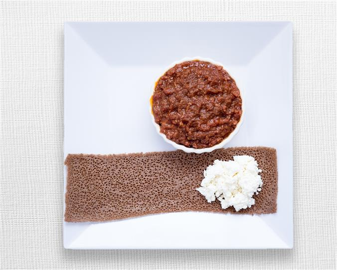 Finely minced extra lean beef cooked to the temperature of your choice seasoned with mitmita and mixed with Kibe spiced butter, served with injera and cottage cheese