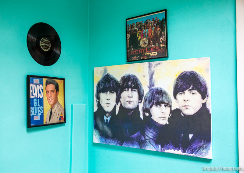 Evlis Presley G I Blues and Beatles posters and artwork on turquoise wall