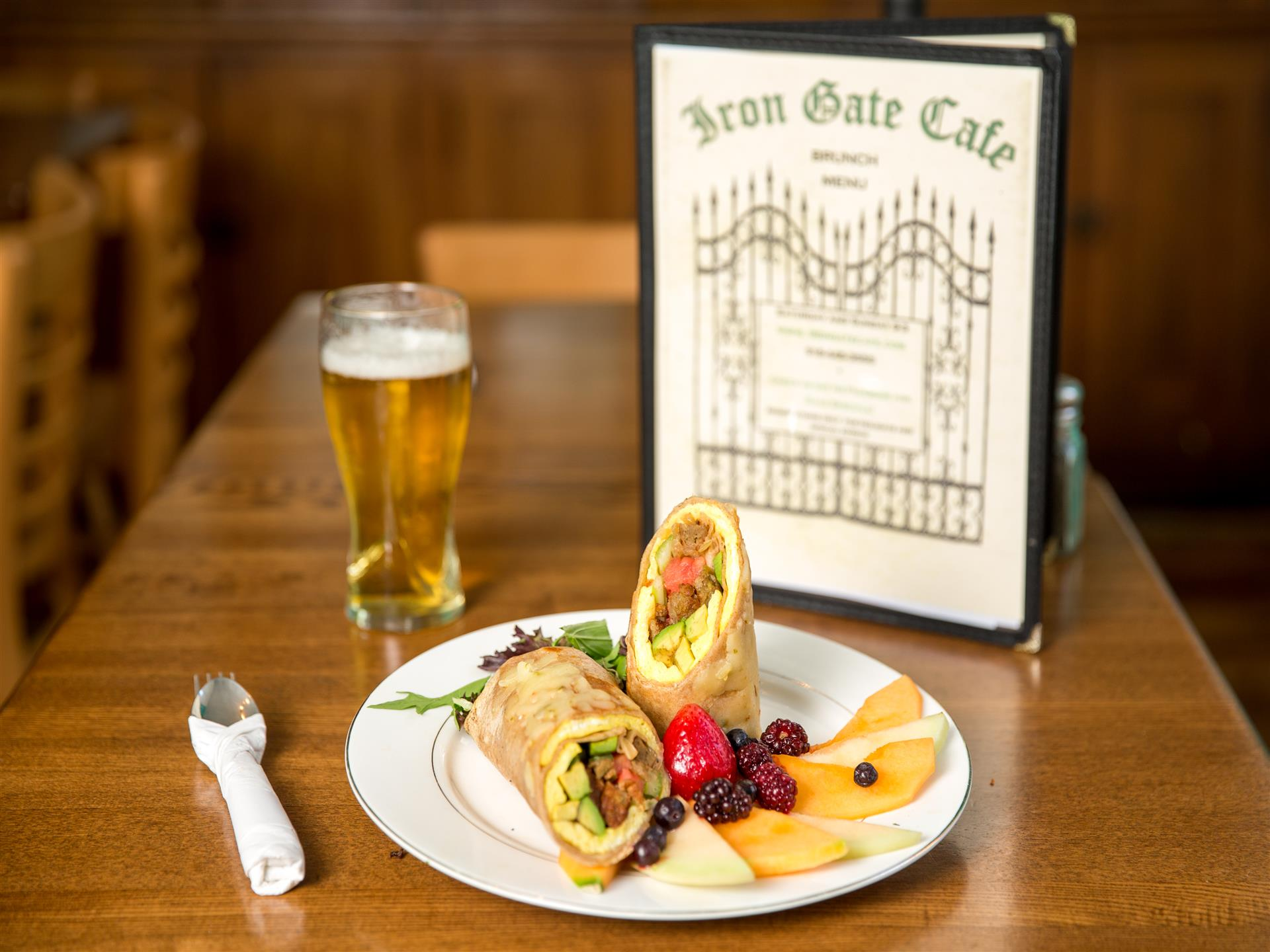 Stuffed wraps with sides of fruit on white plate with beer and menu on light brown table.