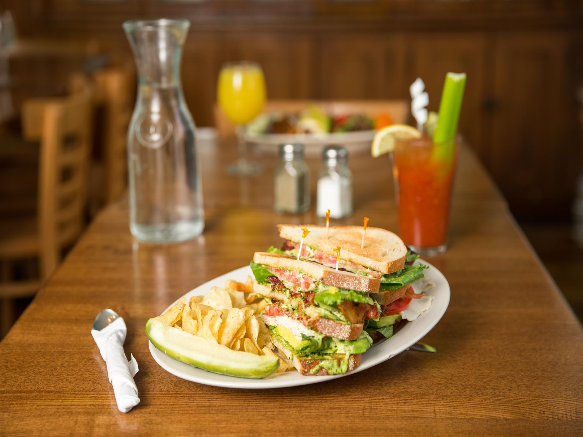 Club sandwiches, chips, pickle, salt and pepper shakers, bloody mary with celery and water carafe on light brown table