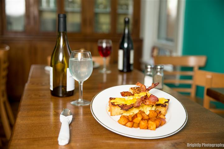 French toast sticks topped over bacon and potatoes