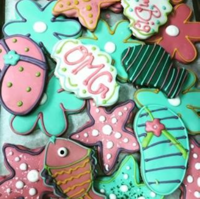 cookies in the shape of flip flops, starfish, fish, flowers, and cookies that read OMG