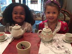Two children sitting at table with teapots and coloring pages