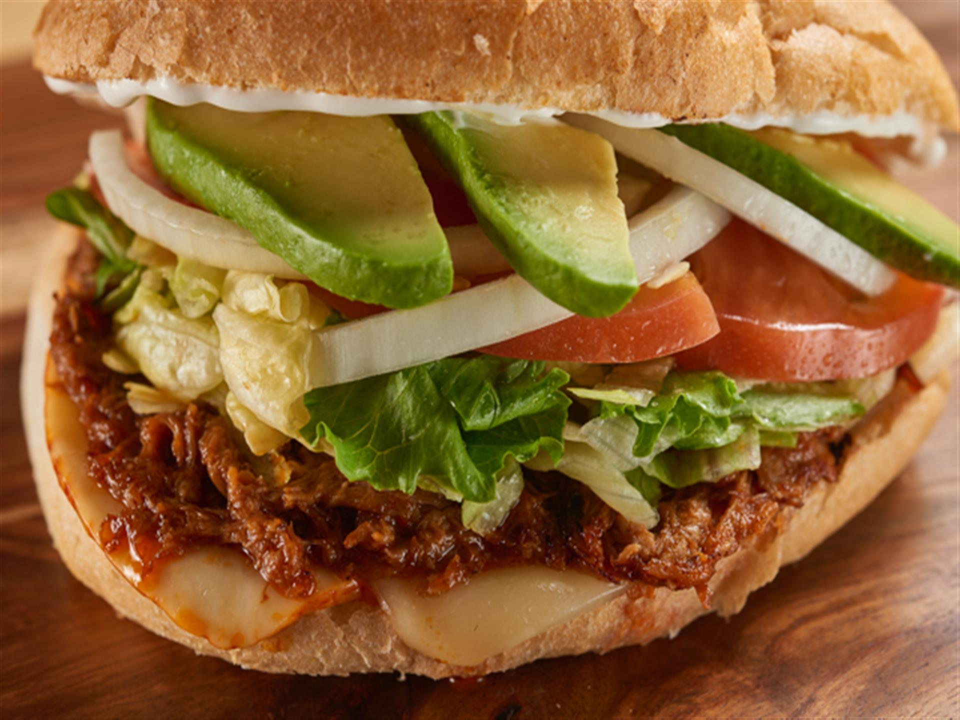 Mexican sandwich with pork, lettuce, tomatoes, onions, avocados