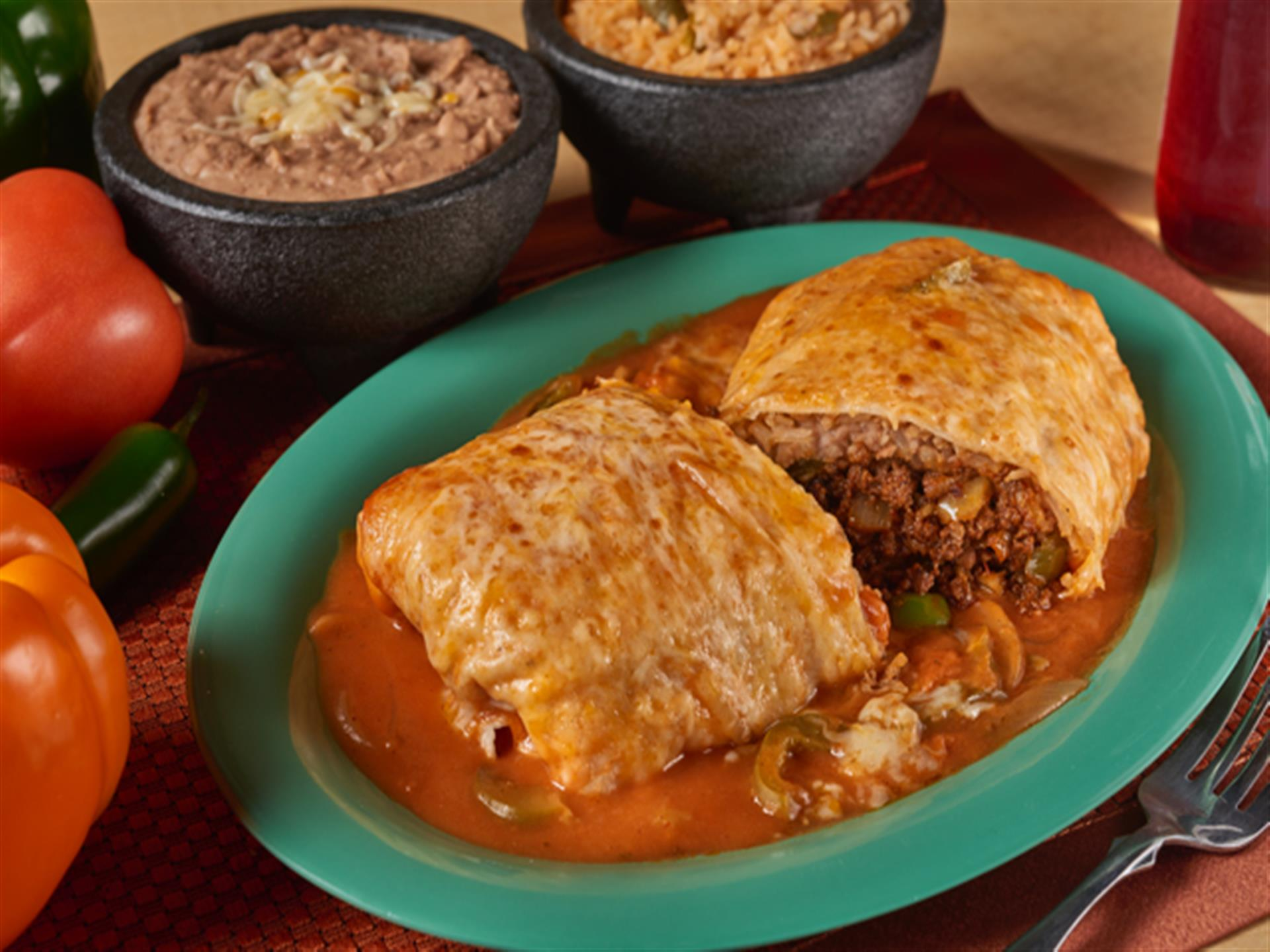 Mexican cuisine - dough stuffed with beef. Rice and refried beans on the side