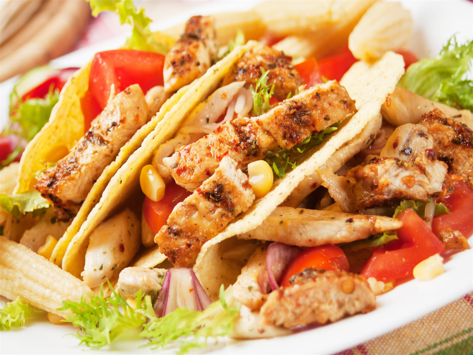 Three chicken tacos with corn, onion, lettuce and tomatoes
