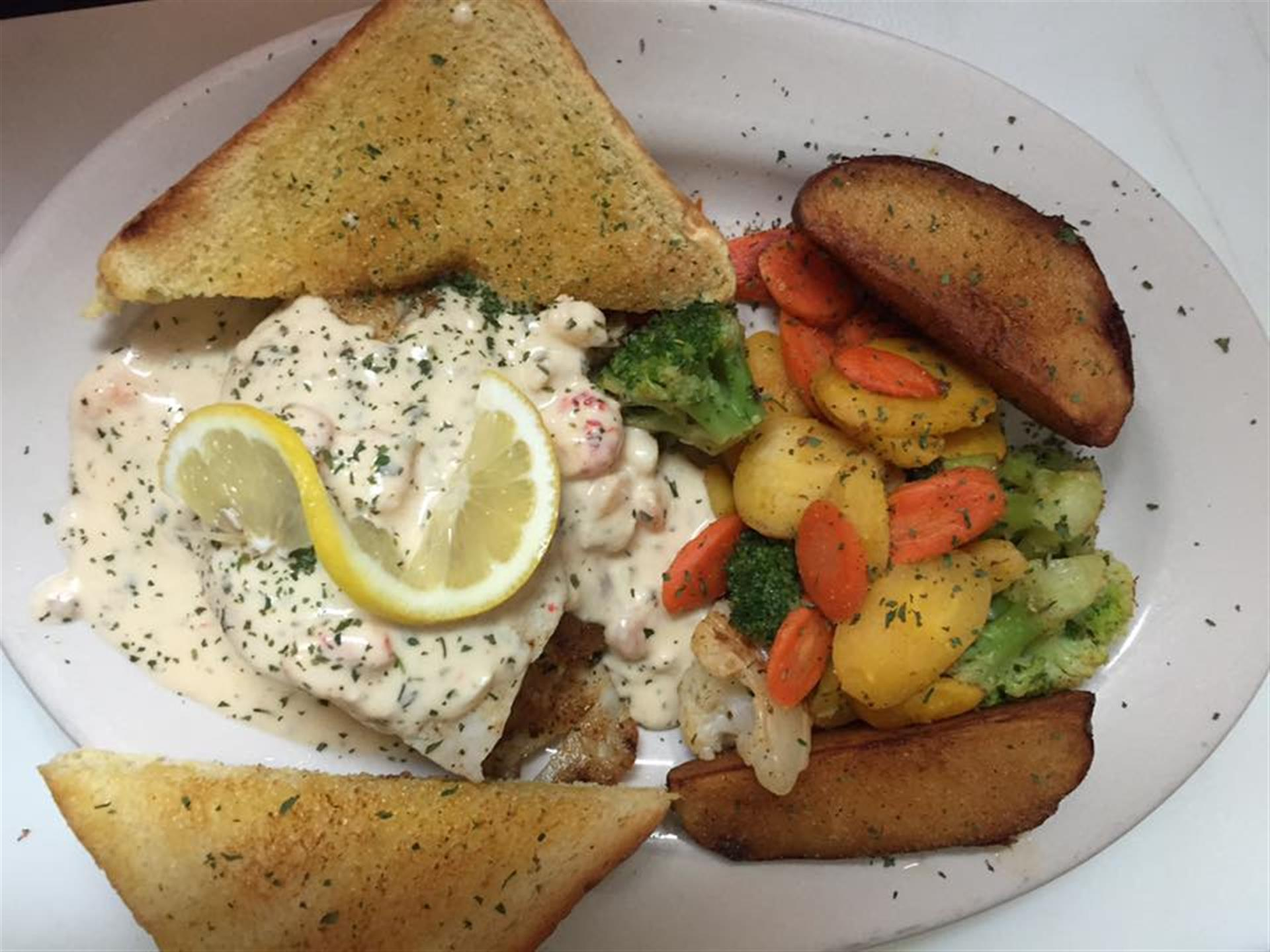 Seafood with white cream sauce, vegetables and garlic toast