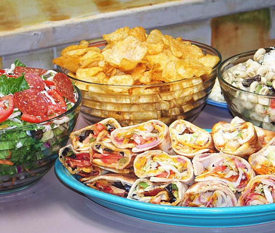 Variety of wraps, salad, chips in bowl
