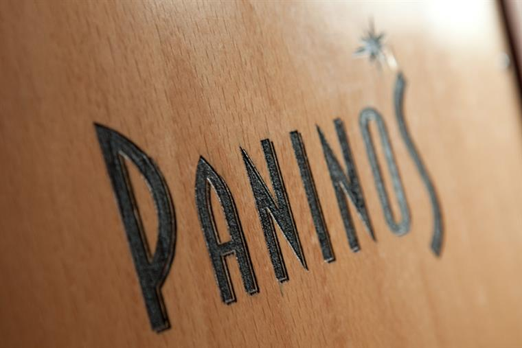 Closeup of engraved wood sign reading Paninos