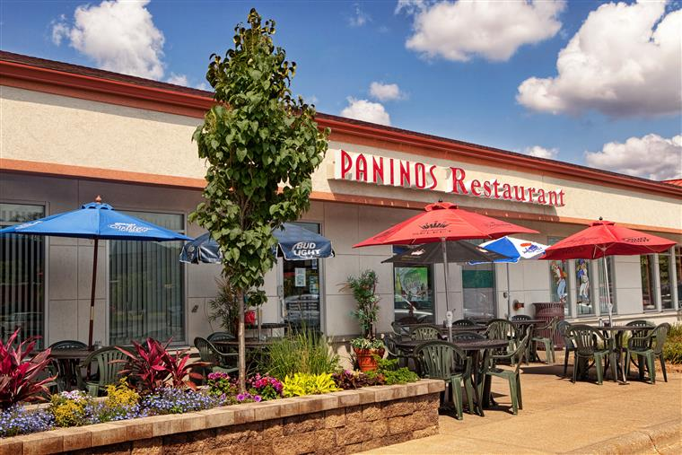 Paninos storefront with outdoor seating on nice day