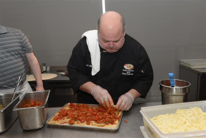 Chef adding toppings on pizza