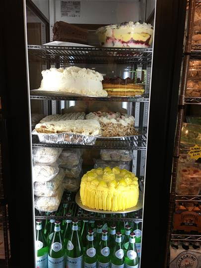 A fridge full of dessert cakes