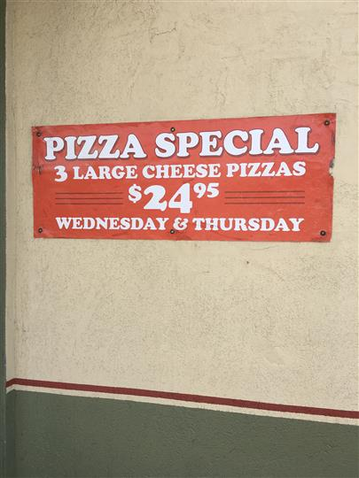 A Sign with the pizza specials of wednesday and thursday: 3 large cheese pizzas $24.95