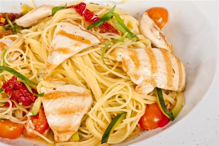 Pasta dish topped with grilled chicken and cherry tomatoes