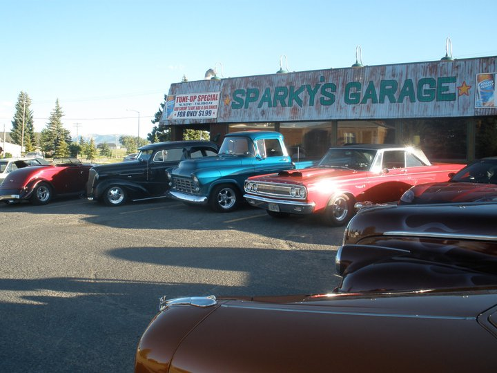 Exterior view of Sparky's Garage from parking lot with vintage cars