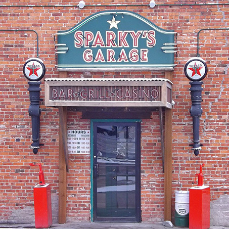 "The front door of the brick building with a sign that says ""Sparky's Garage, Bar, Grill, Casino."