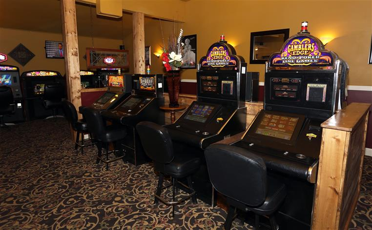 Casino machines lined up in  row with chairs