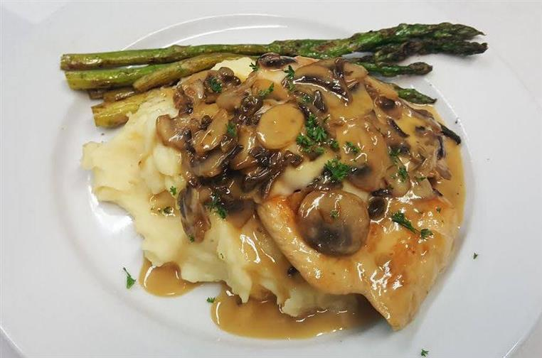 Chicken over mashed potatoes with mushrooms and side of asparagus.
