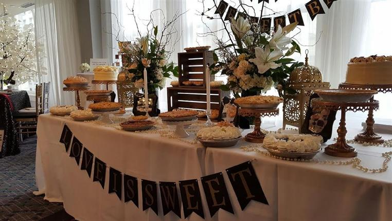 Banquet table at event with elegant pies, cakes, desserts.