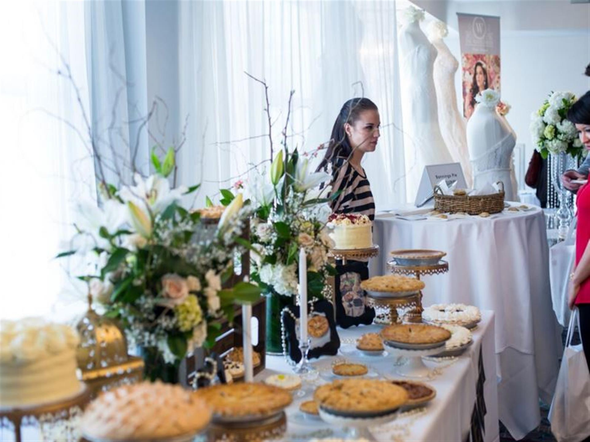 Woman standing at far end of table of decorative cakes and pies on display.
