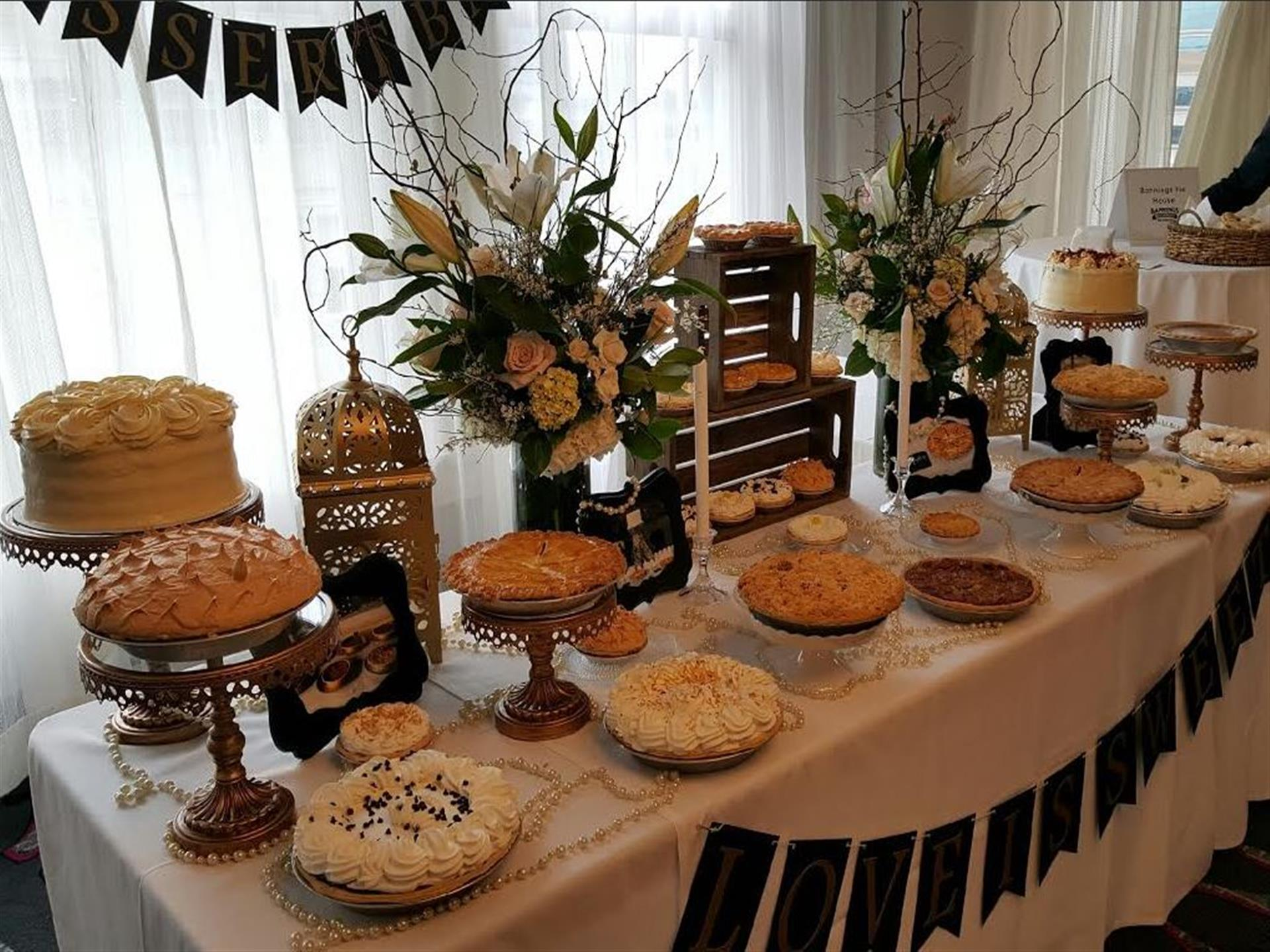 Decorate cakes and pies on display on clothed table.