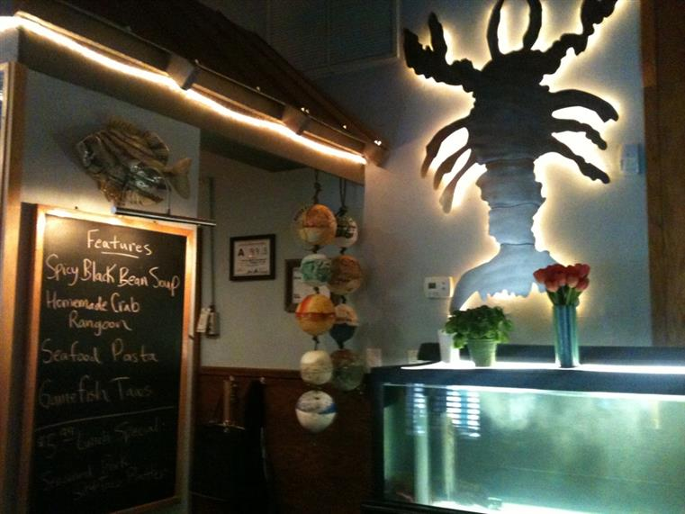 Features on blackboard. Lobster tank and lobster artwork on wall.