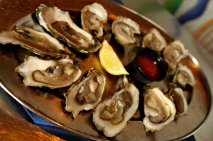 Oysters on half shell with lemon and cocktail sauce on silver tray