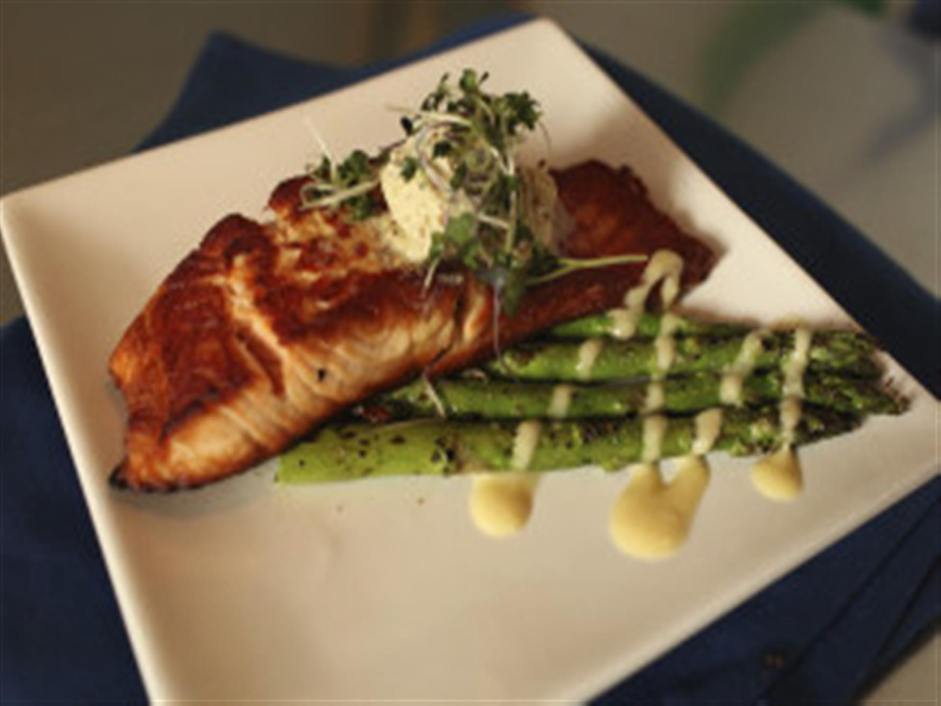 Salmon over asparagus in white dish.