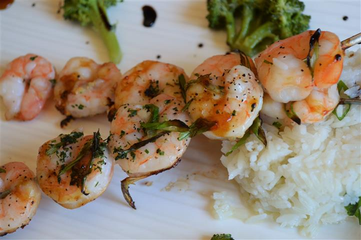 Grilled shrimp on skewers with rice and broccoli