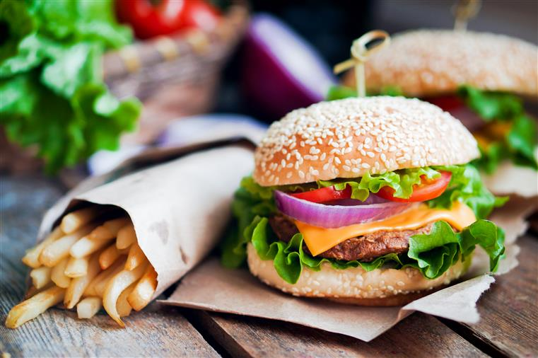 Cheeseburger with lettuce, onion, tomato on seeded bun next to cone of french fries on wooden table