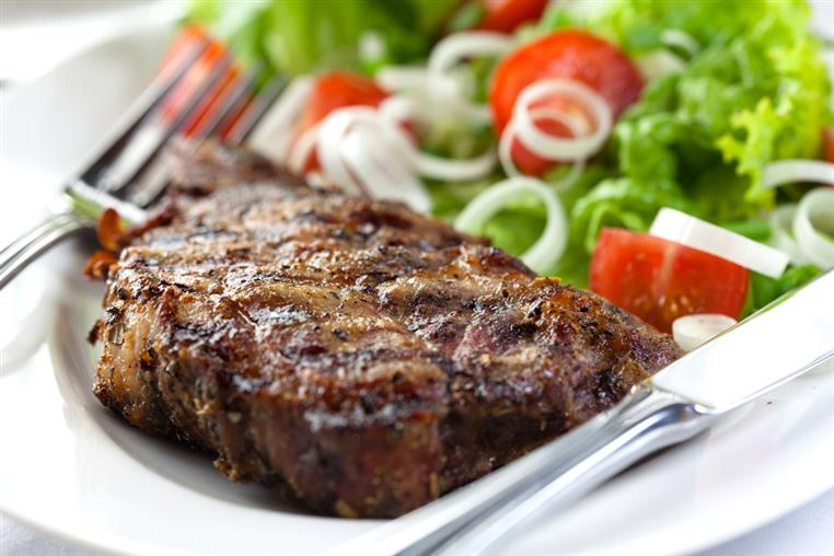Steak and salad on white plate