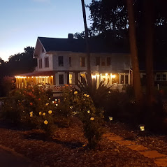 Evening image of Rose Plantation with lit up porch lights