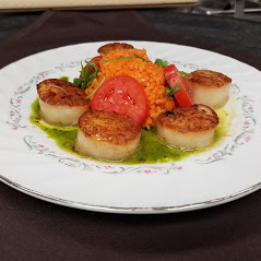 Scallops and red rice on white plate