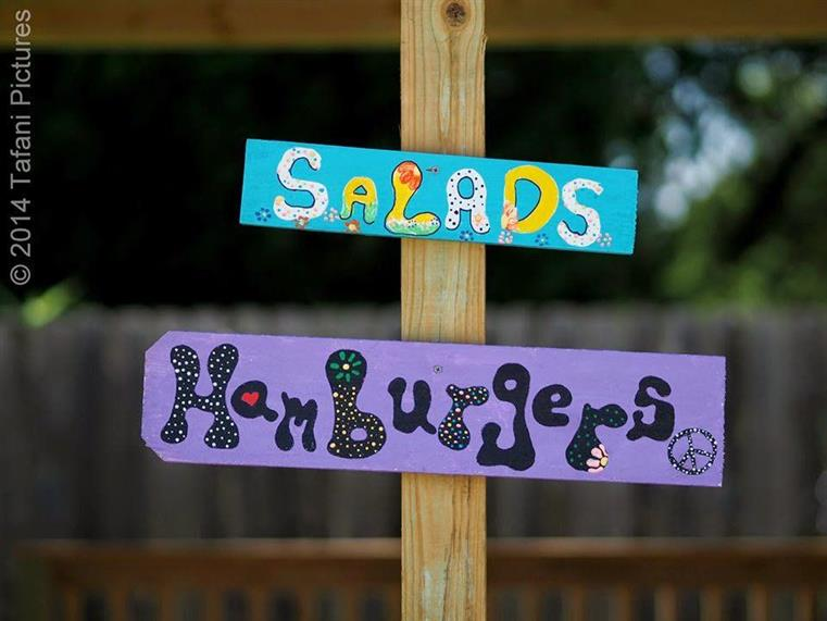 hand-painted signs that read salads and hamburgers