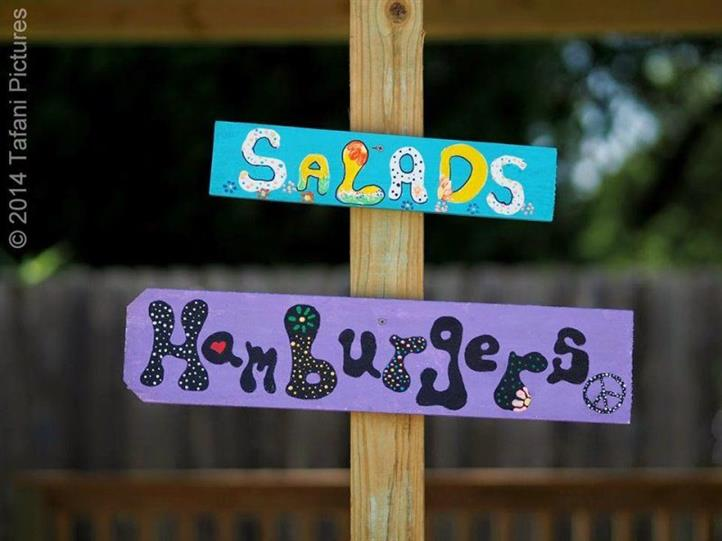 Two painted signs for salads and hamburgers