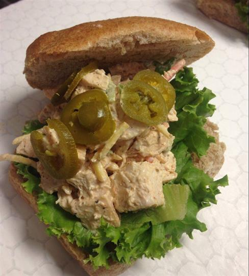 A wheat bread sandwich with tuna salad, pickles and lettuce