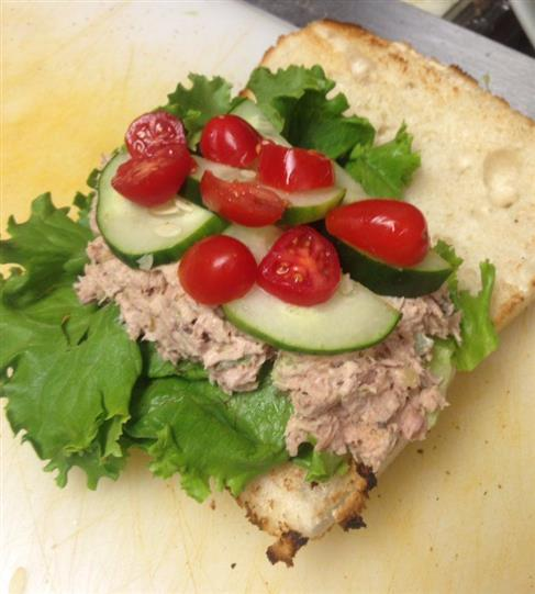 An open faced tuna sandwich with lettuce, cherry tomatoes and slices of cucumber