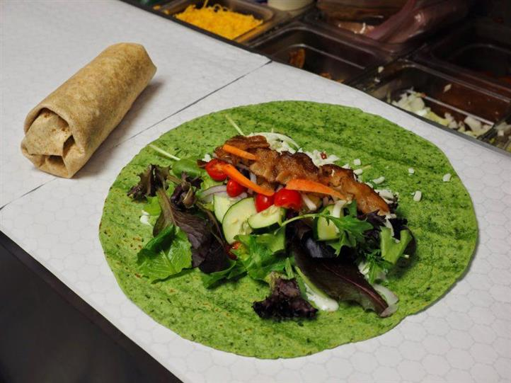 An open faced wrap sandwich with fresh veggies and meat next to a wrap