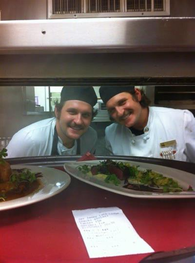 Two smiling cooks posing for photo