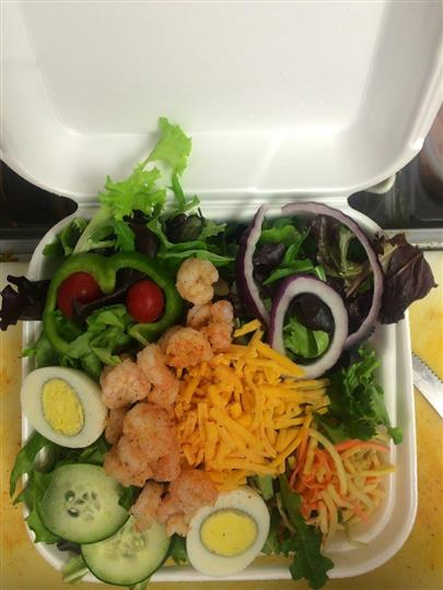 A catering basket with fresh salad with hard-boiled egg and shrimp