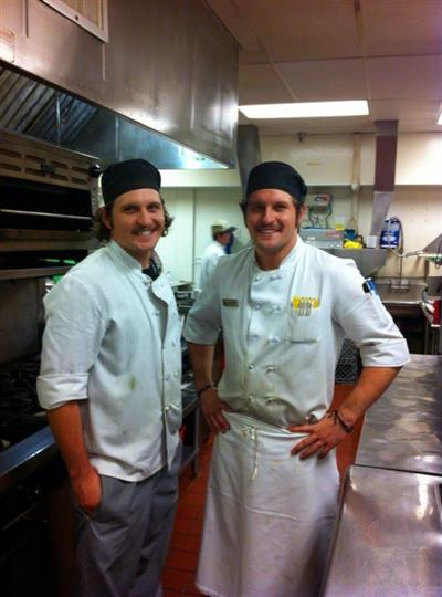 Two chefs posing for photo inside the kitchen