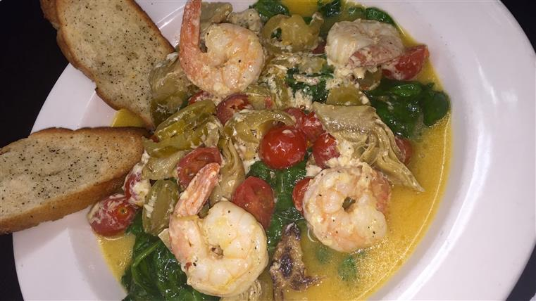 grilled shrimp with artichokes, tomatos, basil with a butter sauce and garlic bread
