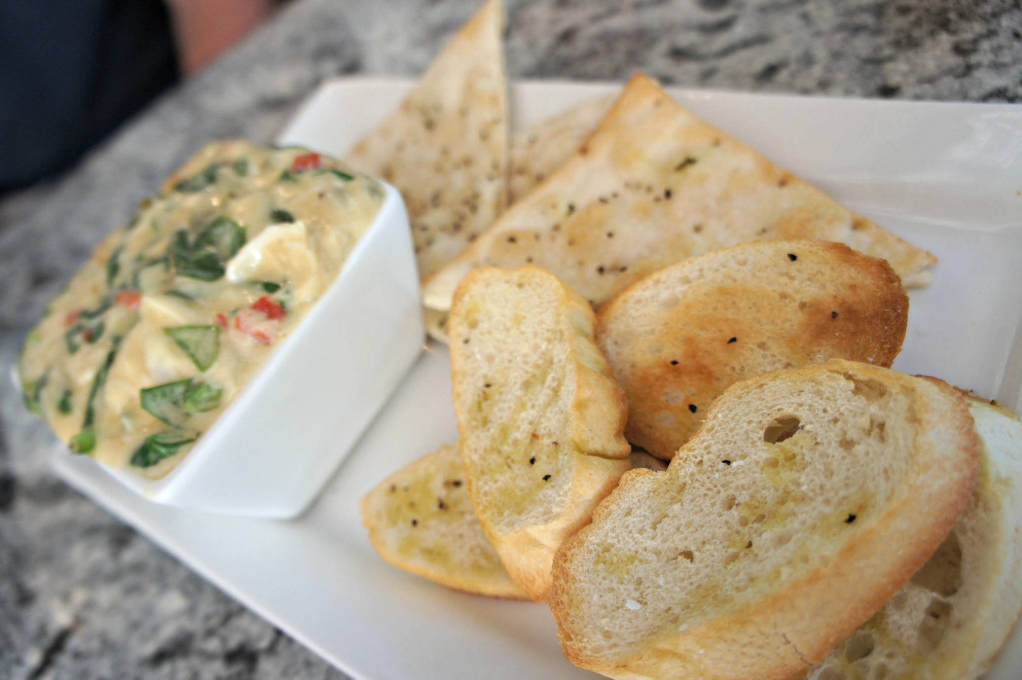 Grilled bread and pita bites served with a side of dipping sauce