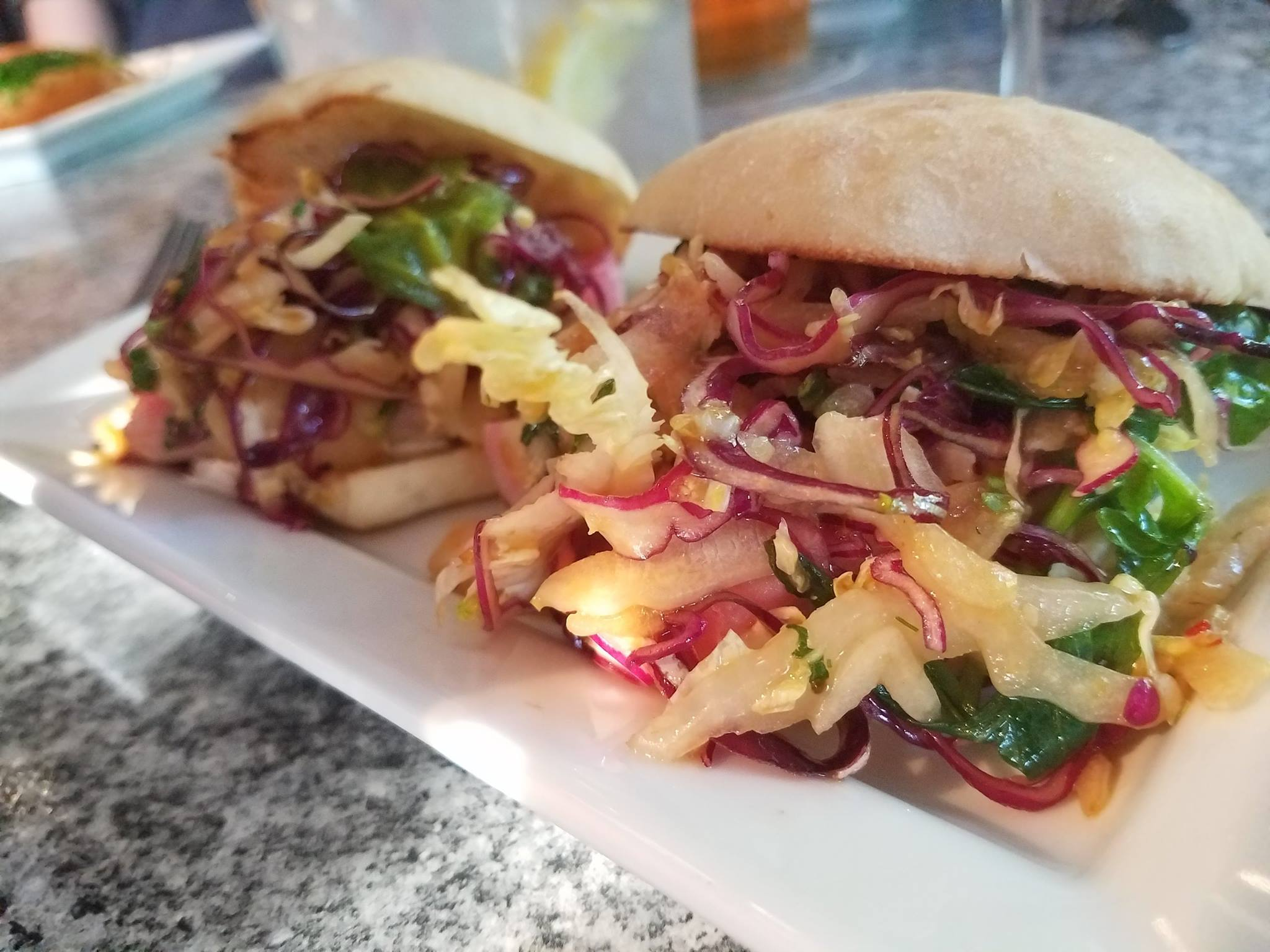 Two buns filled with heaping sauteed vegetbles and srispy slaw served on a white plate