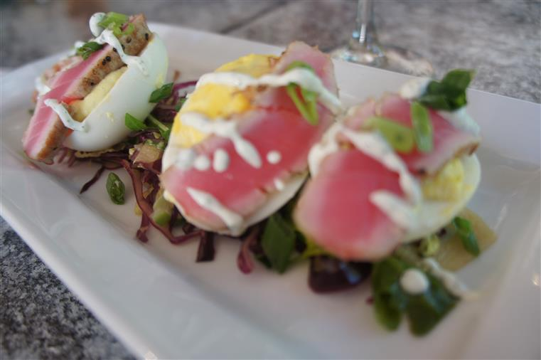 Three wasabi deviled eggs topped with seared ahi tuna and served on a bed of arugula