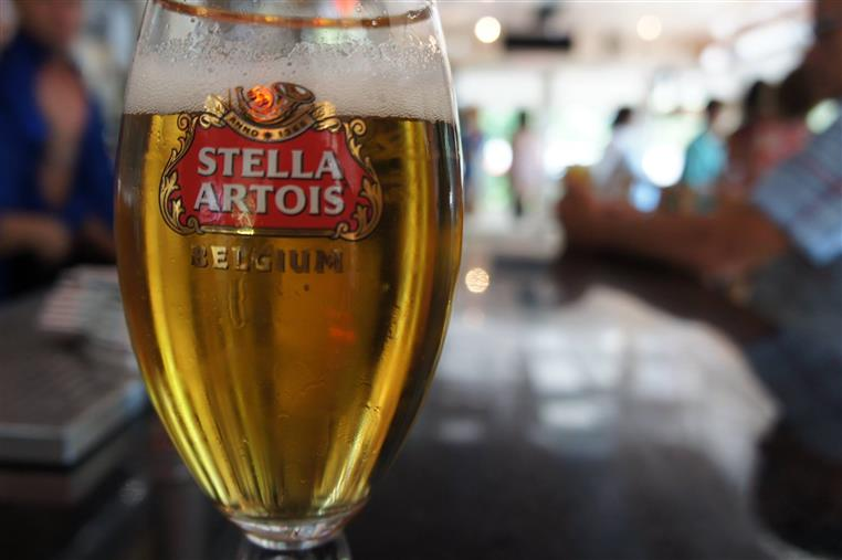 A Stella Artois glass filled with beer on the table with people dining in the background